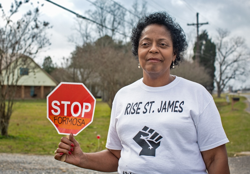 Sharon Lavigne stands outside holding a small stop sign and wearing a white t-shirt reading 'RISE ST. JAMES' and a closed fist