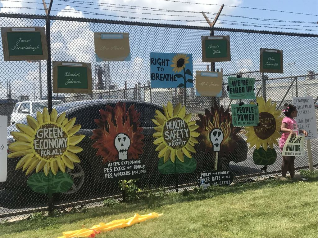 Hand painted posters and murals of sunflowers and skulls remembering community members lost to pollution line a chainlink fence outside the PES Refinery.