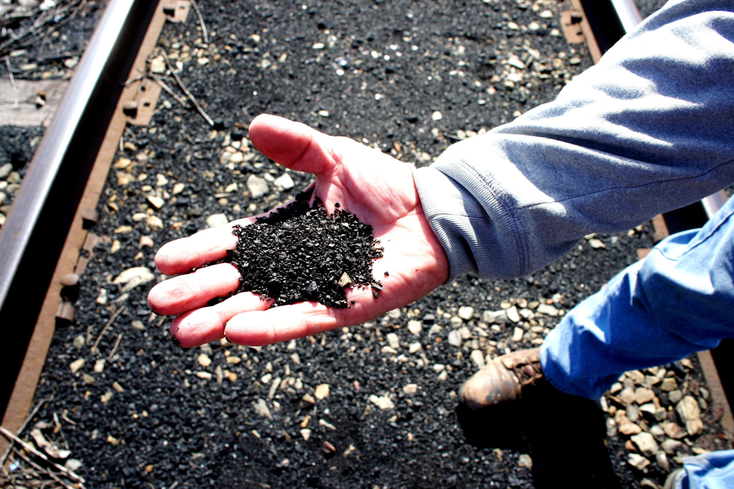 Pet coke covers the railroad tracks that are a border between the backyards of Southeast Side, Chicago families and KCBX's terminal.