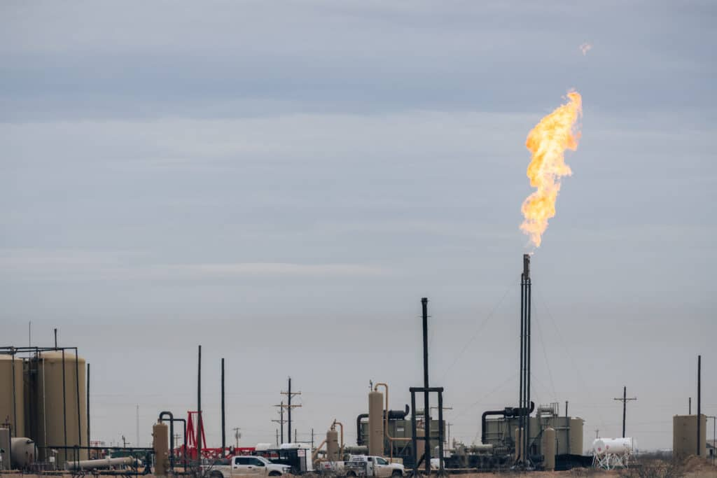 A methane flare burning at an oil and gas site with various tanks and pipes in the Permian Basin