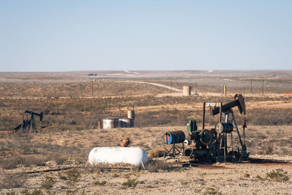 Several old pumpjacks dot the dry flat landscape of the Permian Basin