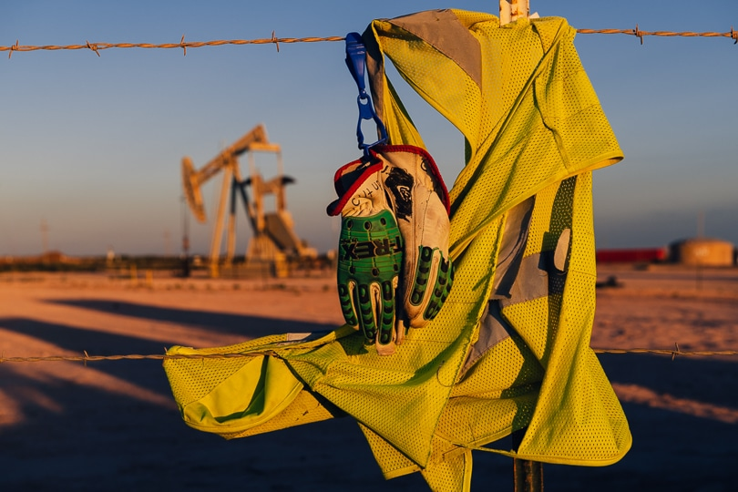 A laid-off oilfield worker's vest and gloves hang on a fence post in front of an idled pump jack in Eddy County, New Mexico at sunset.