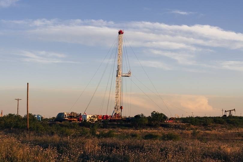 Drilling rig in West Texas prairie grasses with pumpjacks in the background