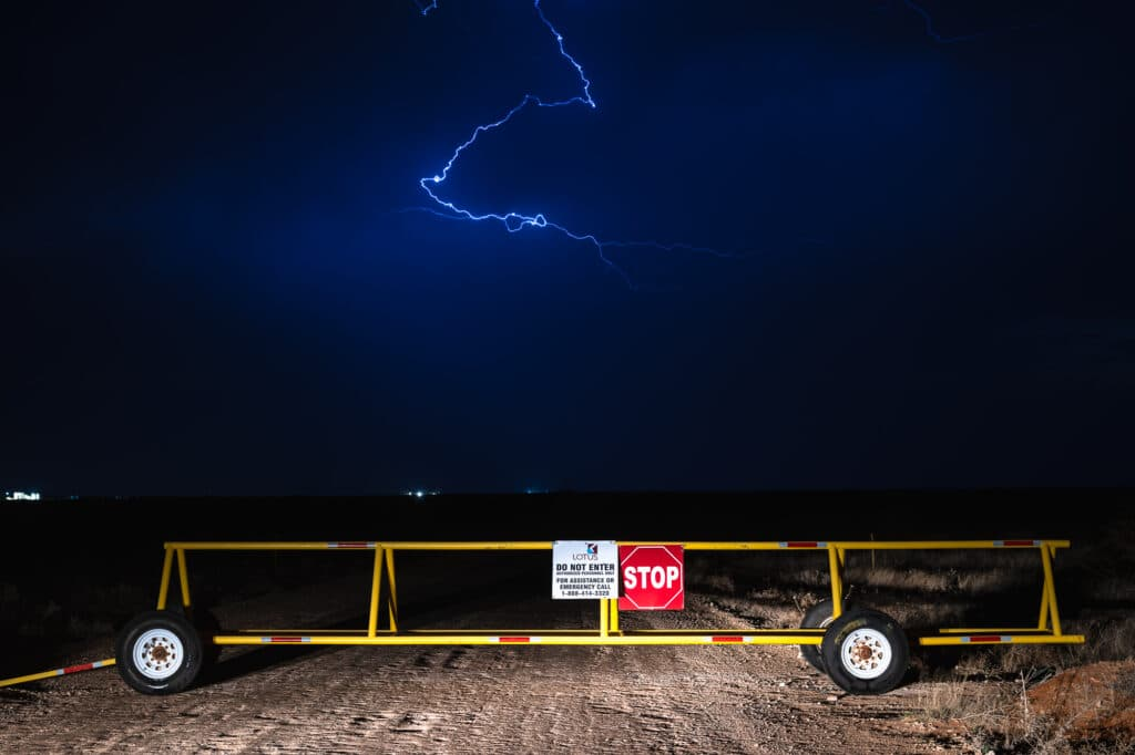 Lightning strikes over Lotus LLC disposal facility mobile gate with a stop sign over a dirt road.