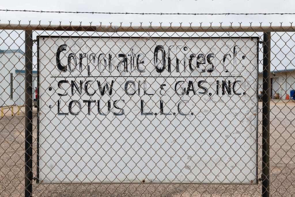 Large white sign with faded black paint with text 'Corporate offices of Snow Oil and Gas Inc, Lotus LLC' behind a chainlink fence