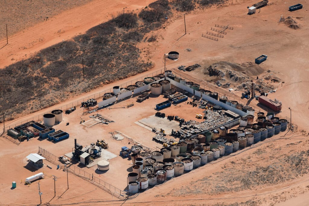 Aerial view of industrial site with dozens of open tanks holding oilfield pipe and other waste and barrels stacked up in the desert.