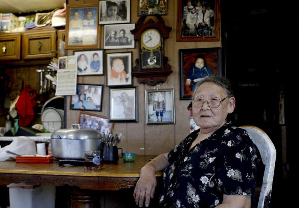 Lucy Adams sits at a table in front of a wall of family photos