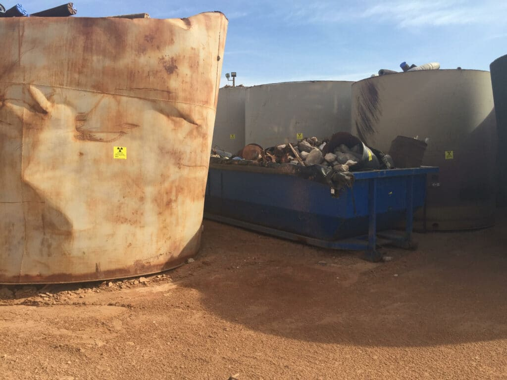 Large rusted and dented white tank next to a blue dumpster with piles of debris and white tanks with pipe sections visible, all sitting on red-dirt desert ground