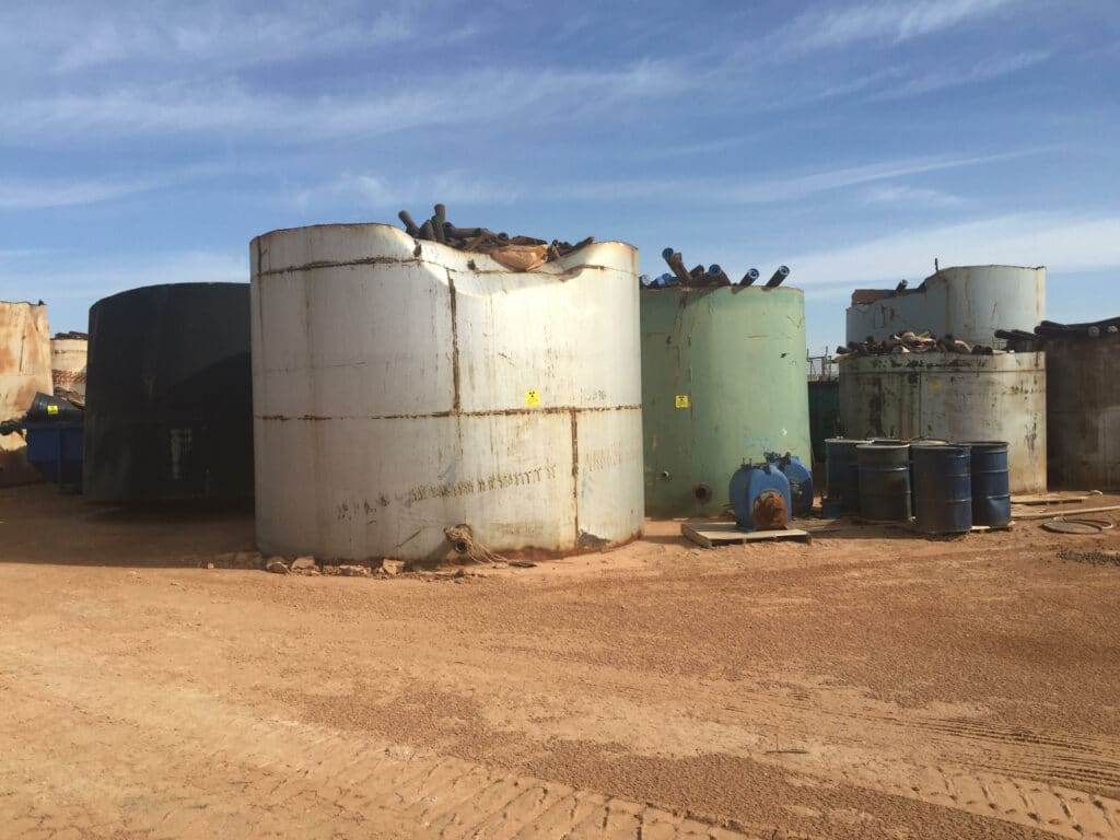 Large, rusty, and damaged white, gray, and green tanks hold oilfield pipe waste, with blue steel drums and dumpster nearby.