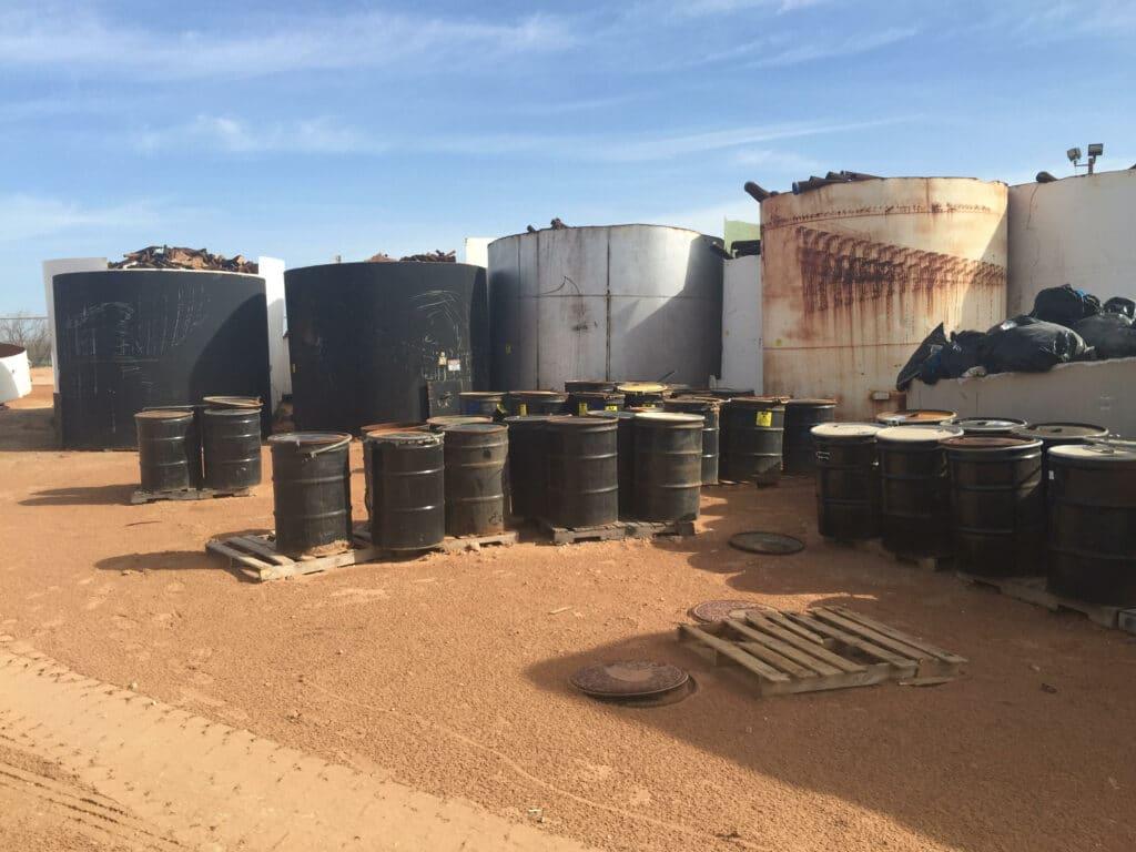 Black barrels on wooden pallets by large rusted white and blue tanks with pipe sections sticking out the top, on a red-dirt desert ground