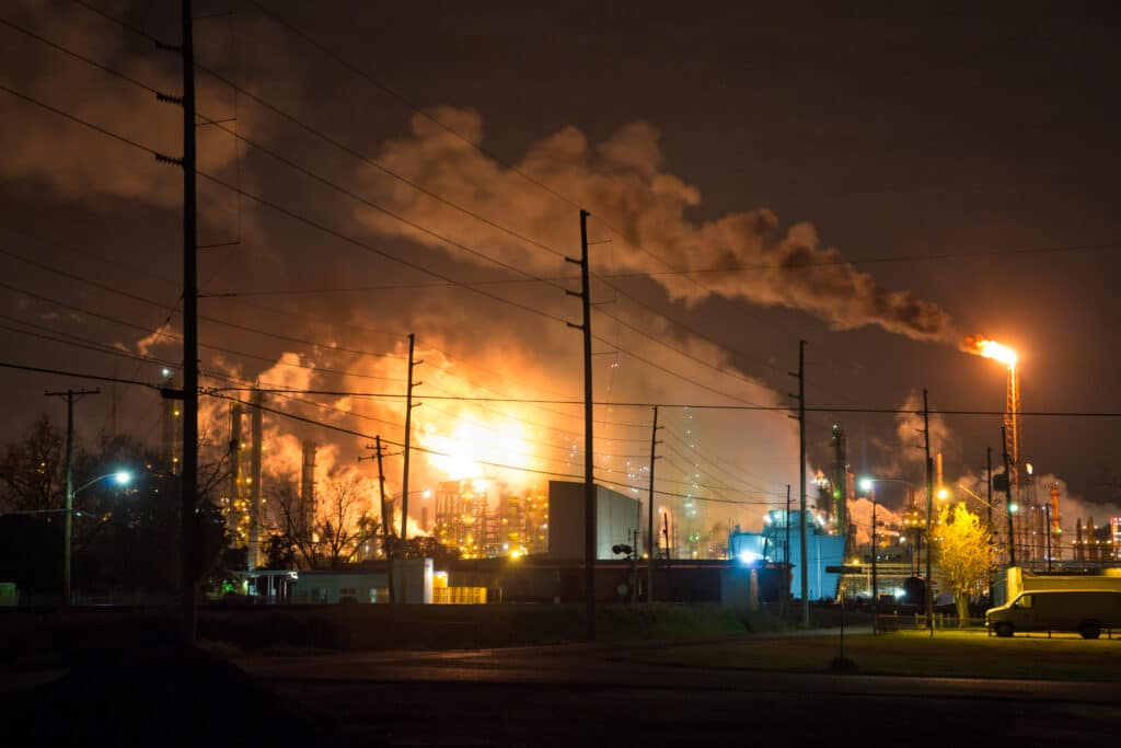 A bright fiery flare lights up a smokey sky over the industrial site of a Shell refinery.