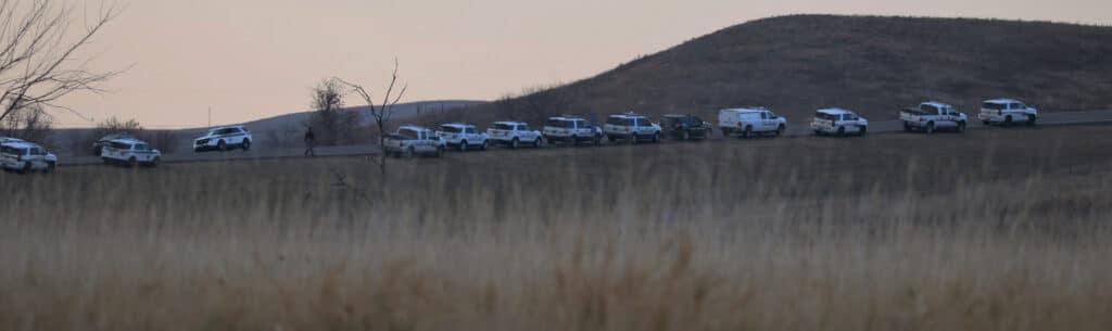 More than a dozen police vehicles line a North Dakota road at sunset