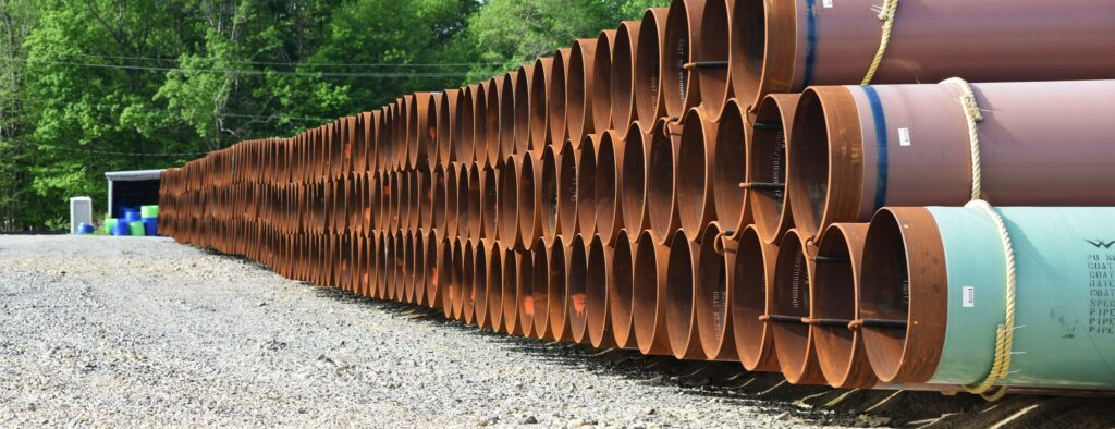 Rust-red and turquoise pipe sections are stacked three high on gravel in a wood part of Ohio.