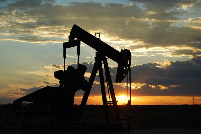 An oil pumpjack seen in profile as sun sets.