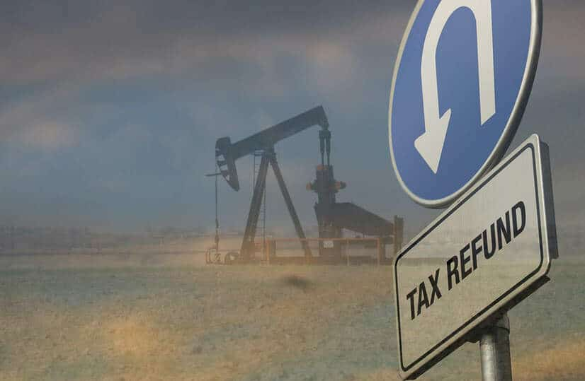 Oil derrick and tax refund u-turn sign overlaid