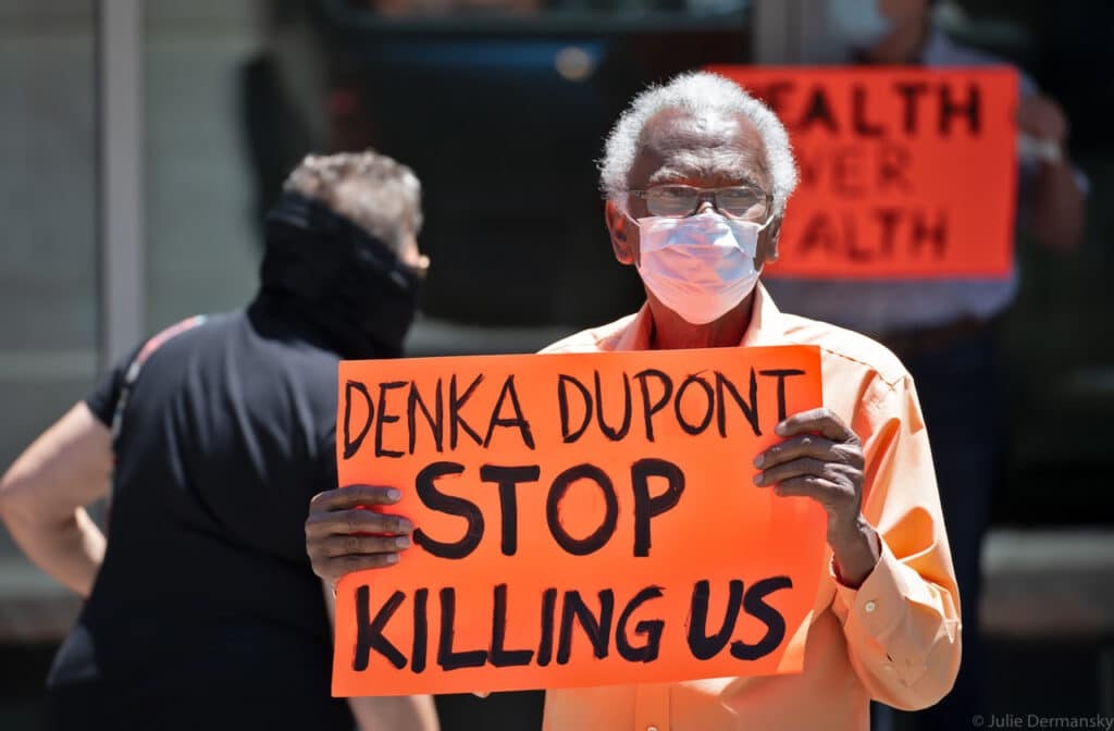An older Black man in a medical mask holds an orange sign with text 'Denka Dupont stop killing us'