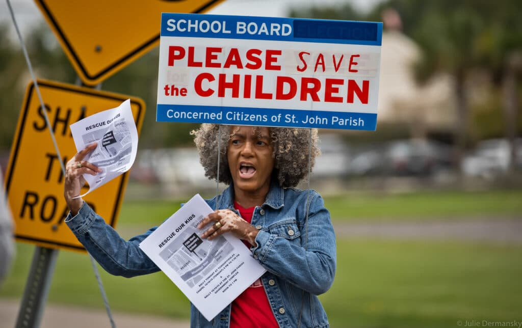 A Black woman with gray in her hair holds signs and flyers about saving children from air pollution while standing outside.