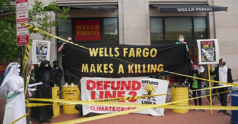 Activists protest banks funding the Line 3 pipeline in front of a Wells Fargo, with yellow caution tape and oil drums and holding banners