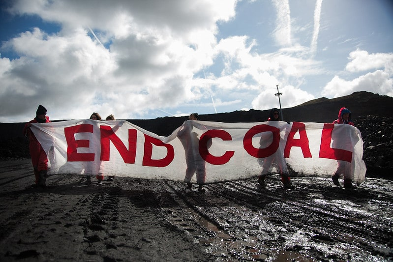 """Activists hold a white banner with red letters reading """"End Coal"""""""