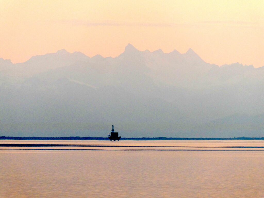 An offshore drilling platform in the distance at sunset with mountains behind.