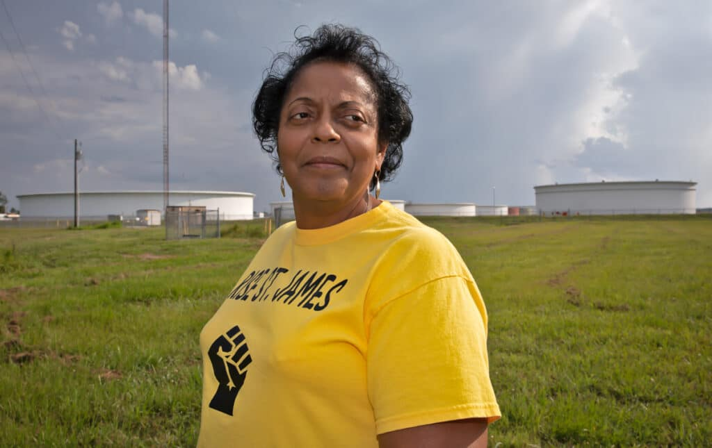Sharon Lavigne, a Black woman wearing a yellow t-shirt with RISE ST. James and a raised fist, in front of a field of oil tanks