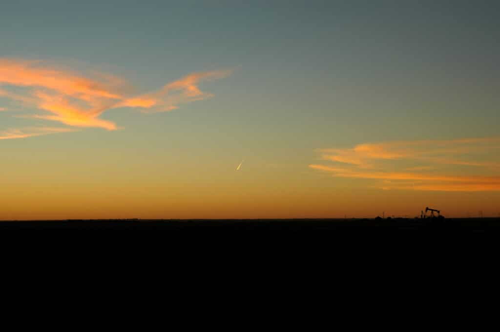 Oil pumpjack in the distance at sunset in a flat plain
