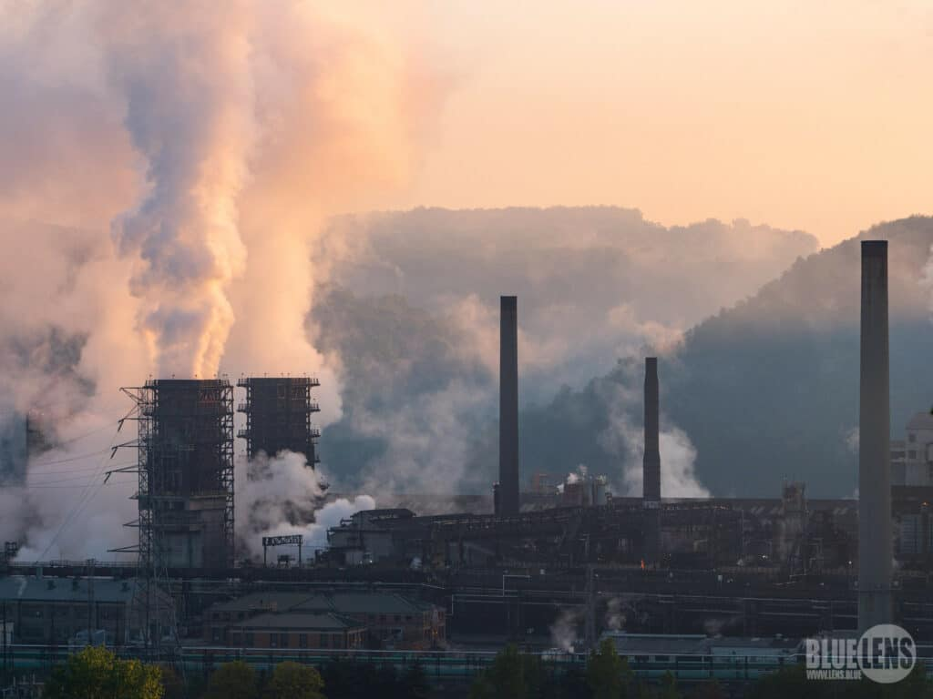 An industrial coke works with thick white smoke billowing out of smokestacks at twilight.