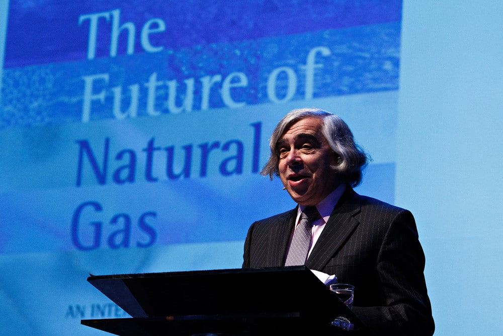 """Ernest Moniz standing at a podium with """"The Future of Natural Gas"""" on a blue background projected behind him."""