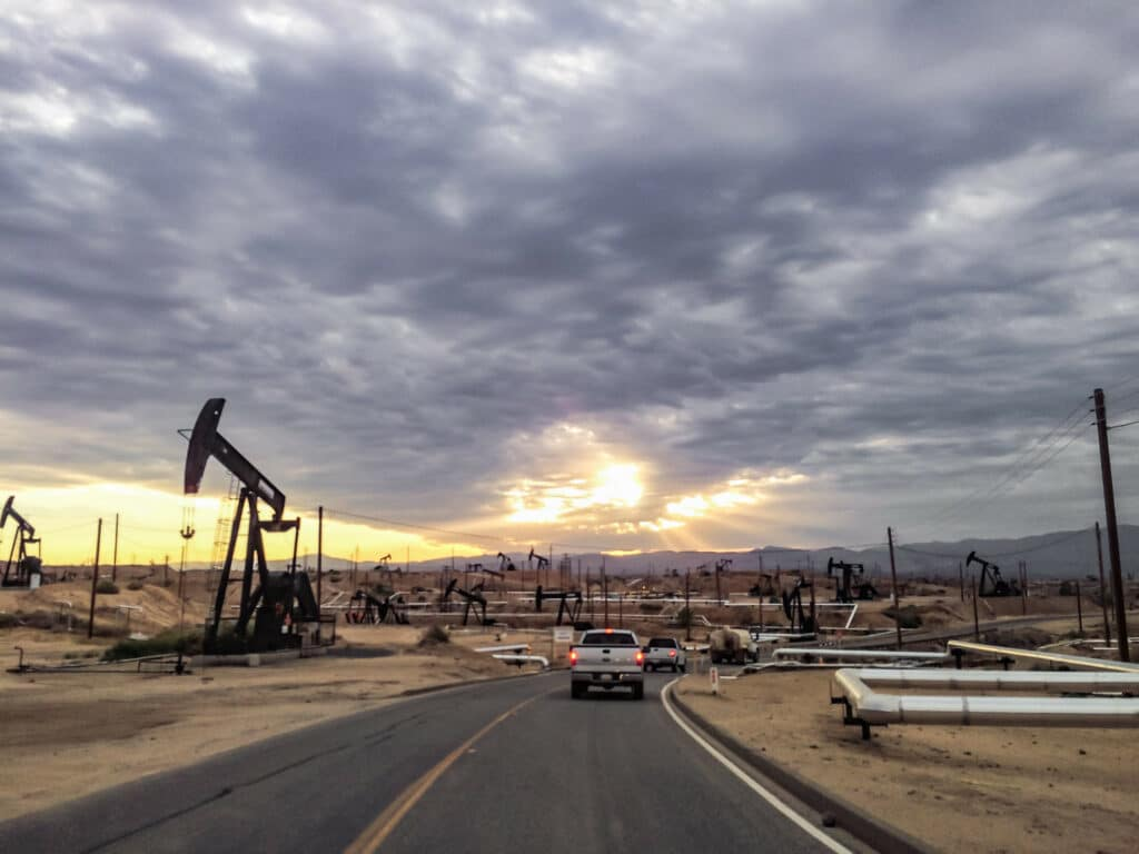 Vehicles drive down a highway through an arid oilfield at sunset