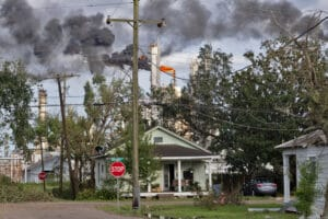 Green house with trees and black smoke coming from a burning refinery flare