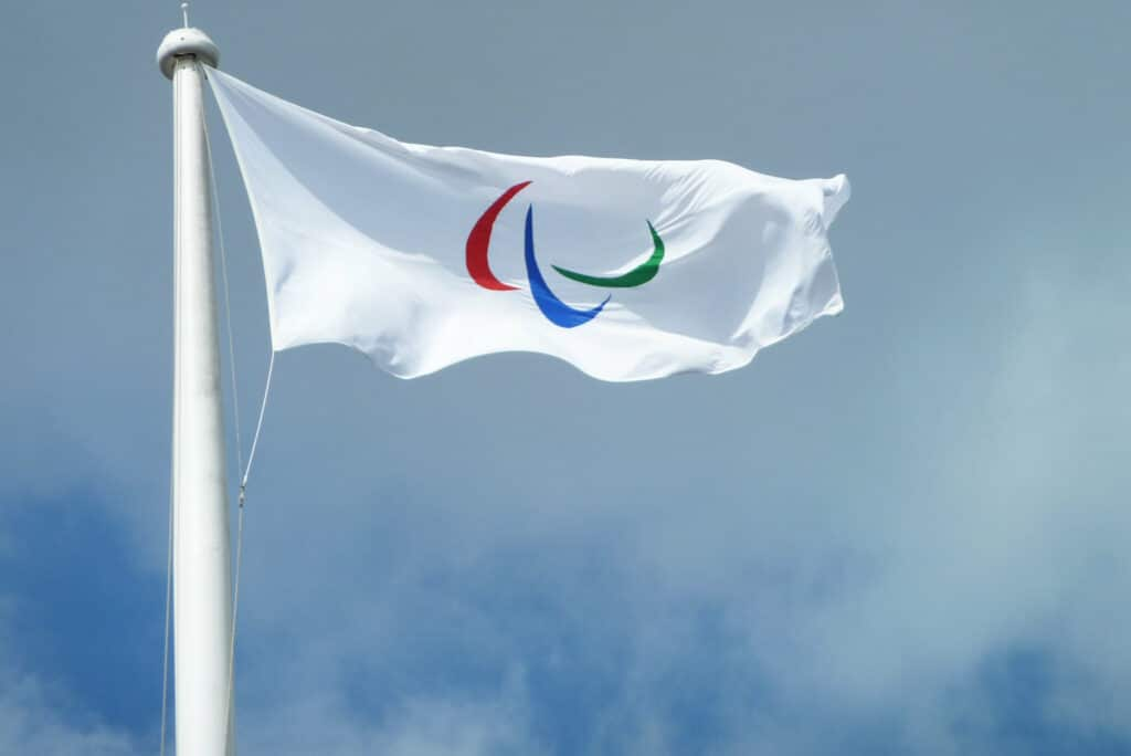 A white flag with red, blue, and green arcs
