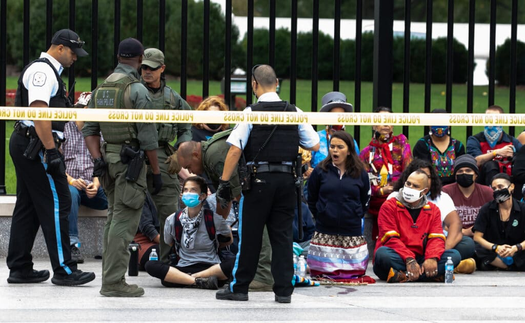 Group of seated climate protesters confronted by police by White House fence behind yellow do-not-cross tape