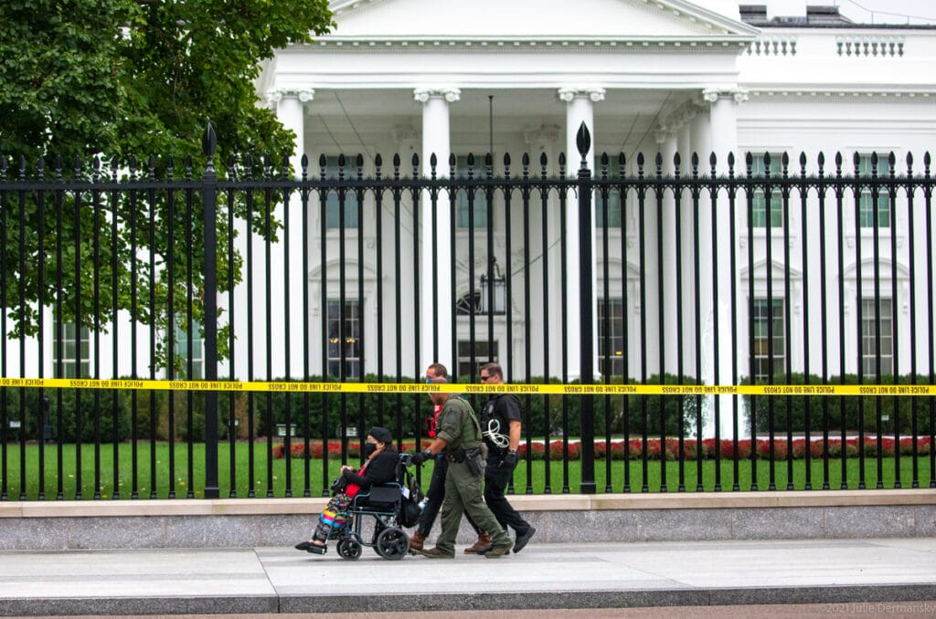 An Indigenous woman in a wheelchair is pushed by two policemen in front of a fence and the White House