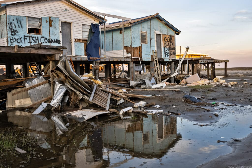 Damaged fishing camp houses and floodwaters at sunset