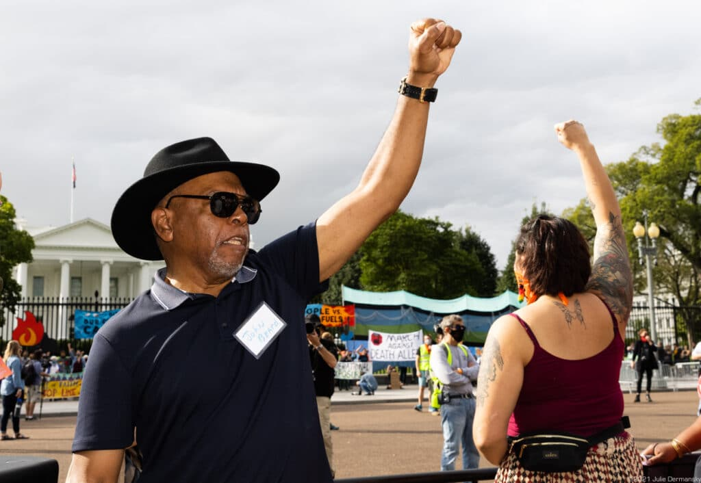A Black man in a blue t-shirt and black wide-brim hat raises his fist, alongside a white woman in tank top also raising her fist, outside the White House.