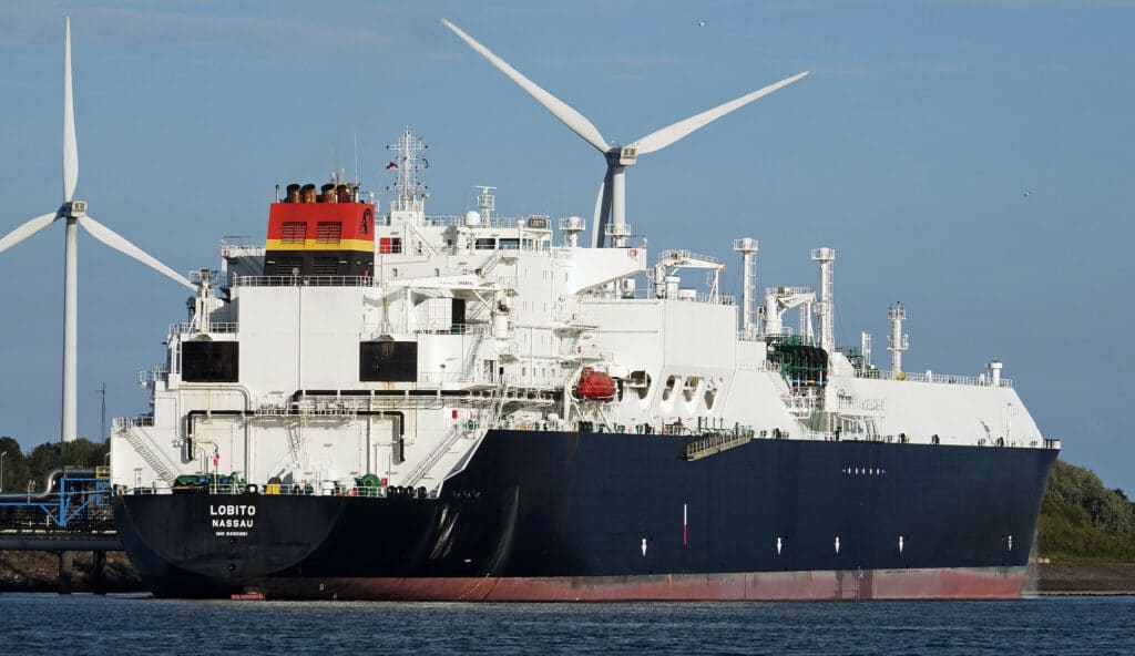 Large LNG tanker vessel passing in front of two white wind turbines