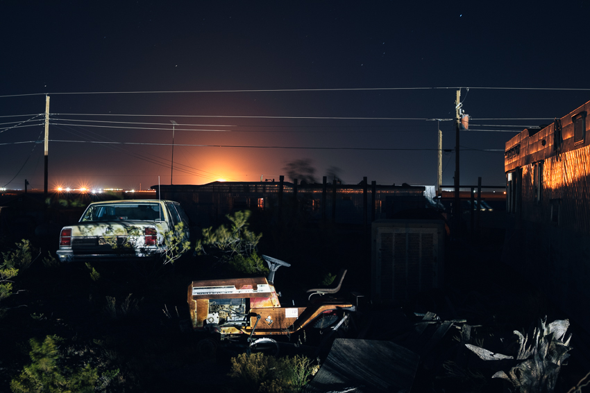 Abandoned camp outside Orla, Texas, lit up by a gas flare and saltwater disposal facility.