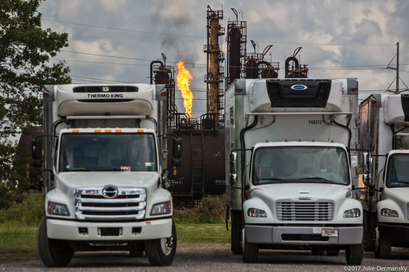 Trucks in front of flaring at ExxonMobil Beaumont plant after Hurricane Harvey