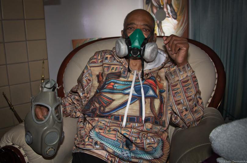 Johnie Perryman wearing a respirator in his home in Clairton