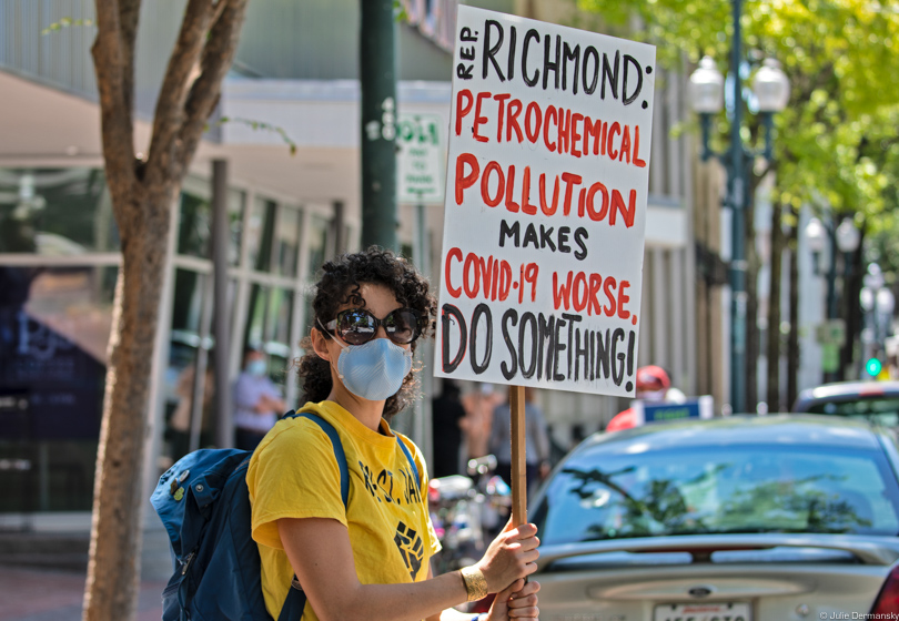 Activist holding a sign pressuring Cedric Richmond on petrochemical pollution in his district