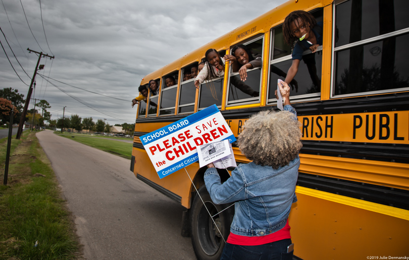 Lydia Gerard hands kids on a school bus information about pollution concerns