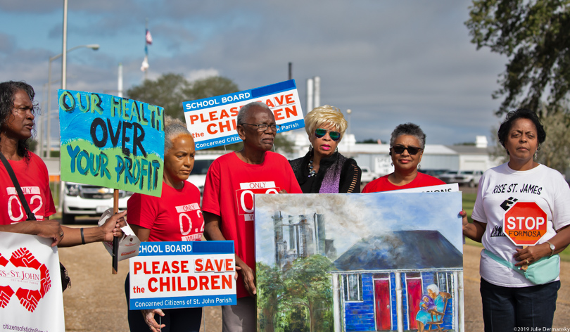 Concerned Citizens of St. John hold signs and protest outside Denka's neoprene plant