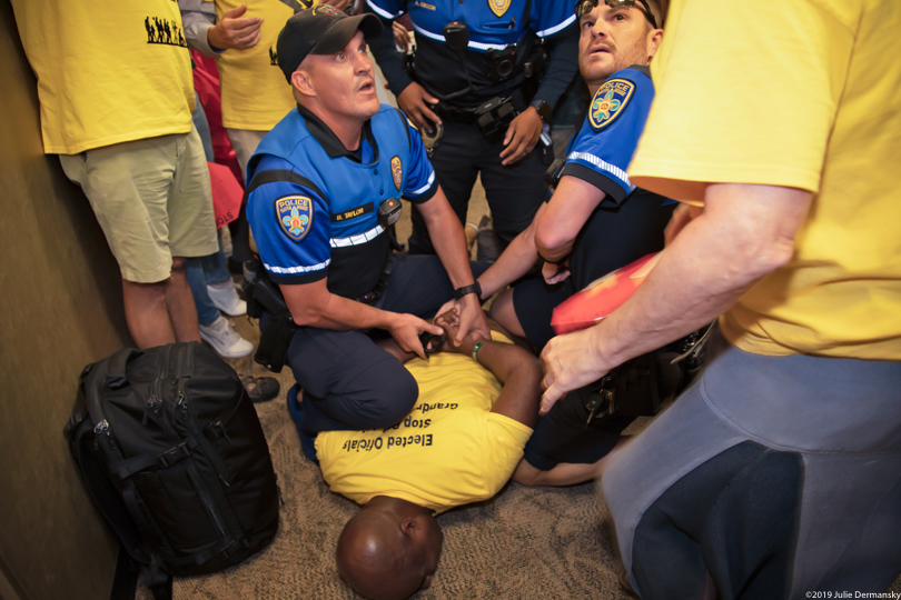 Pastor Gregory Manning being pinned to the ground by two police officers