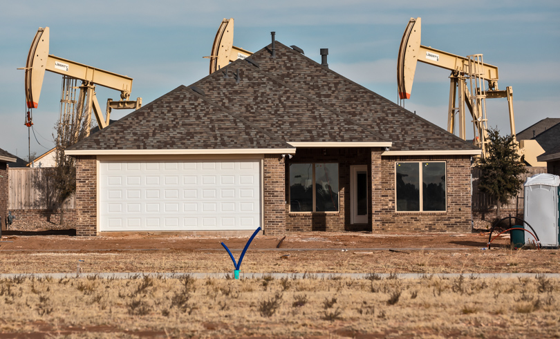 Three oil pumpjacks visible behind a newly constructed house in the Permian Basin