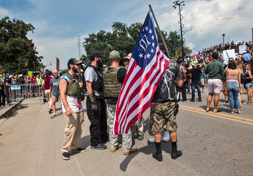 Protesters in military gear and holding a Three Percenter flag at a rally for a Confederate memorial in Louisiana