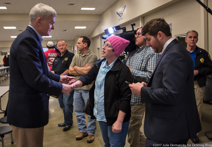 Sen. Cassidy shakes hands with a woman in a pink hat at a town hall meeting.