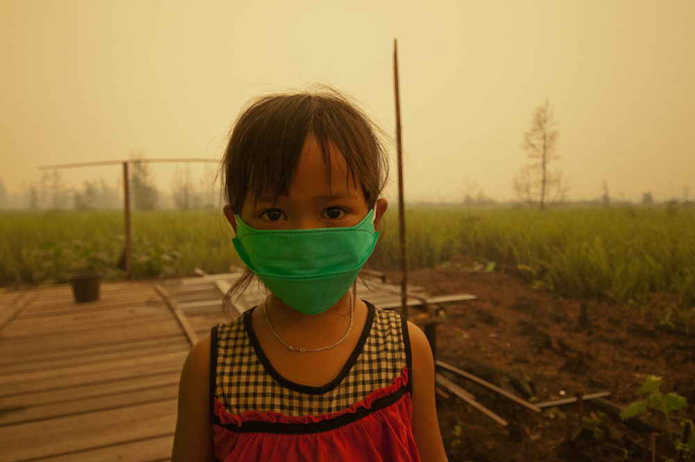 Child with mask from toxic smoke from peat land fires in Indonesia.