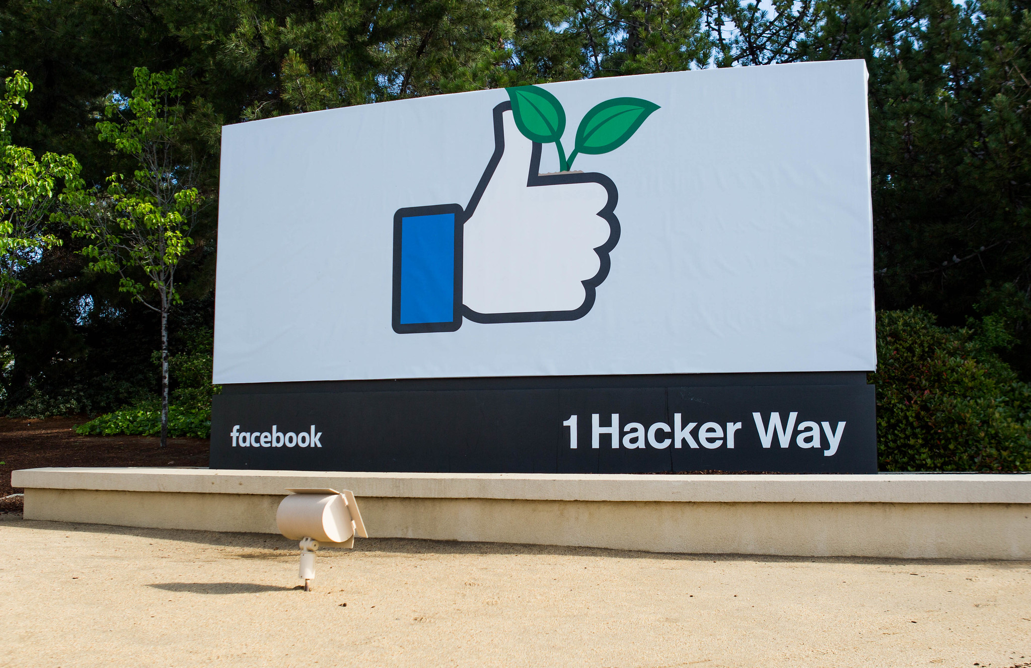 Sign with the thumbs-up 'like' icon with green leaves at the entrance to Facebook HQ in Menlo Park
