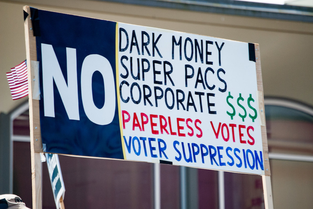 A parade in Everett, Washington, in 2017 features an anti-dark money sign
