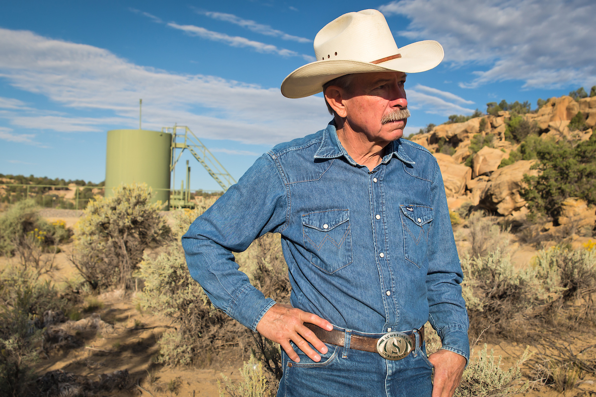 Don Schreiber on his ranch in Blanco, New Mexico, in front of a gas well re-drilled in 2014 on Bureau of Land Management land he leases.